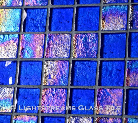 High quality American Made Lightstreams Glass Tile Renaissance Collection II Intense Blue 2.0 glass tiles are a shiny medium true blue on one side, with colorful rainbow iridescent colors on the reverse textured side. This blue tile can also be used for pool tile, spa tile, fountain tile, fire pit tile, wall tile, waterline tile, step marker tile, exterior tile, interior tile, accent tile, iridescent tile, backsplash tile, kitchen tile, bathroom tile, floor tile, spillway tile, and shower tile