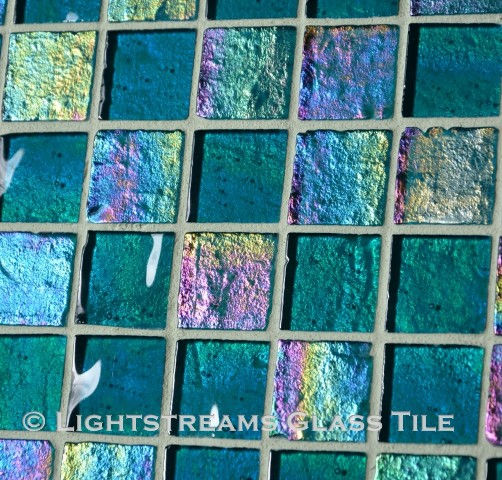 High quality American Made Lightstreams Glass Tile Renaissance Collection II Teal 2.0 glass tiles are rich green / blue in color.  There are beautiful rainbow iridescent colors on the reverse textured side of the tile. This blue tile / green tile can also be used for pool tile, spa tile, fountain tile, fire pit tile, wall tile, waterline tile, step marker tile, exterior tile, interior tile, accent tile, iridescent tile, backsplash tile, kitchen tile, bathroom tile, floor tile, and shower tile