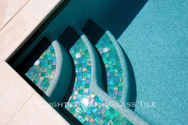 American Made Lightstreams Glass Tile Renaissance Collection Celadon green tile is used on the step of this pool as pool tile, spa tile, step tile, step marker tile, and waterline tile. This photo really shows off the iridescent tile side and the smooth shiny side of Lightstreams signature reversible tile