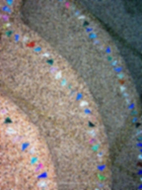 """American Made Lightstreams Glass Tile, Lightstreams Shell Beach Decorative Glass Tile Strands  """"Jewelry for Your Swimming Pool"""", Accent tile that can be used for pool tile, floor tile, spa tile, step marker tile, step accent tile, wall tile, waterline tile, kitchen tile, glass backsplash tile, bathroom tile, and fountain tile. A photograph of Shell Beach glass accent tile strands on natural color pebble-finished swimming pool steps as accent tile step markers"""
