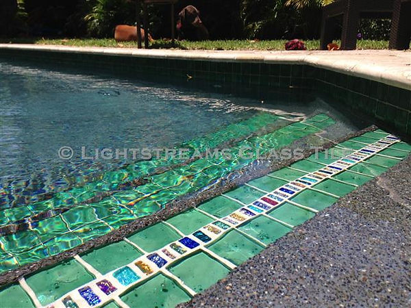 American Made Lightstreams Glass Tile, Strands of Jewel Inlays are bordered by Renaissance Collection Celadon glass green tile to create a lovely pool step marker for this swimming pool also usd for accent tile, pool tile, spa tile, waterline tile, fountain tile, wall tile, step marker tile, kitchen tile, backsplash tile, bathroom tile, and countertop tile