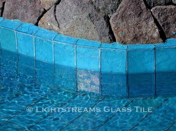 American Made Lightstreams Glass Tile Renaissance Colllection Aqua Blue tile is used as pool tile and spa tile for this outdoor / indoor pool and spa in this luxury swimming pool. Only the iridescent tile side is shown face up in this waterline tile photo of this all tile pool and all tile spa