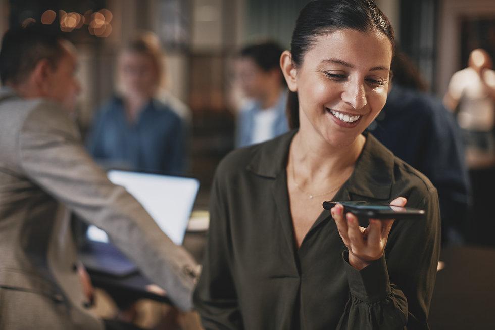 smiling-businesswoman-talking-on-speaker