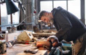 smiling-male-mechanic-repairing-details-
