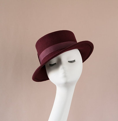 Hand-blocked hat with asymmetrical brim in wine red wool felt