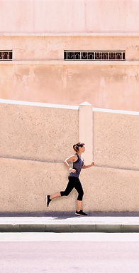 Lady in workout cothes running next to a light coloured wall