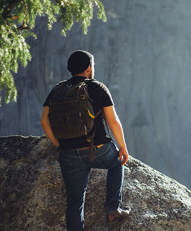 Man with black backpack and beanie climbing over a rock