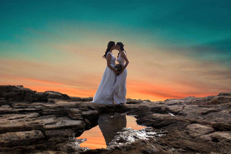 צילומי חתונה מיוחדים - זוג כלות גאות מתנשקות על רקע שקיעה רומנטית בחוף בצת ליד כפר ראש הנקרה