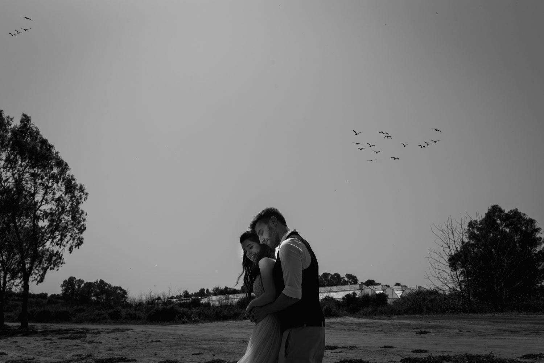 צילומי חתונה מיוחדים בחוות סוסים בשרון, זוג מתחבק על רקע ציפורים עפות