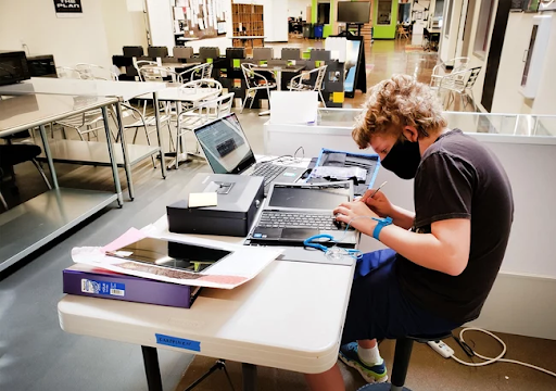 This student is learning to repair computers as part of the school's student-led tech team, an internship opportunity at Compass.