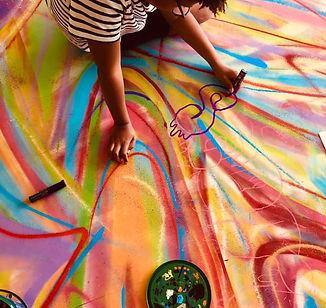 un enfant en train de dessiner aux poscas su une grande toiles multicolore graffé, au cours d'un ateier graffiti réalisé avec le Fjep de passy mont bl