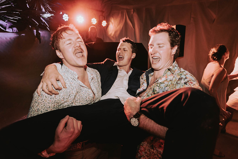 groom held up by two friends with disco lights and dance floor in background