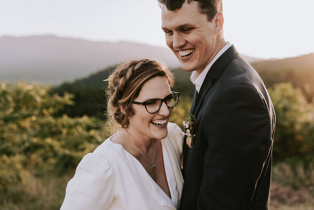 wedding couple laughing with rainforest and sunset in background