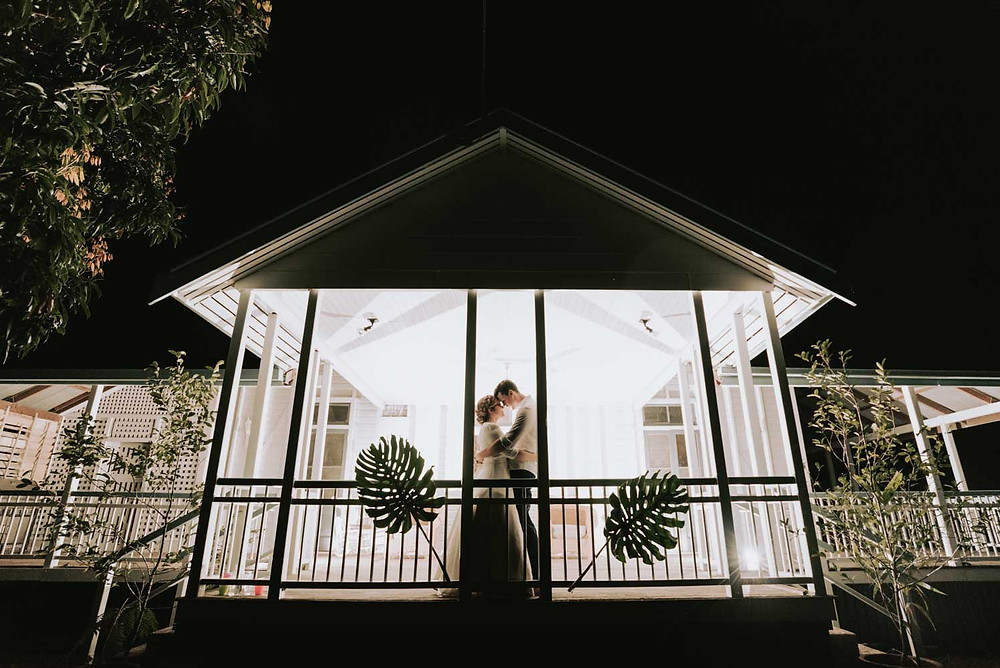 wedding couple embracing on deck of farm house with monstera decorations