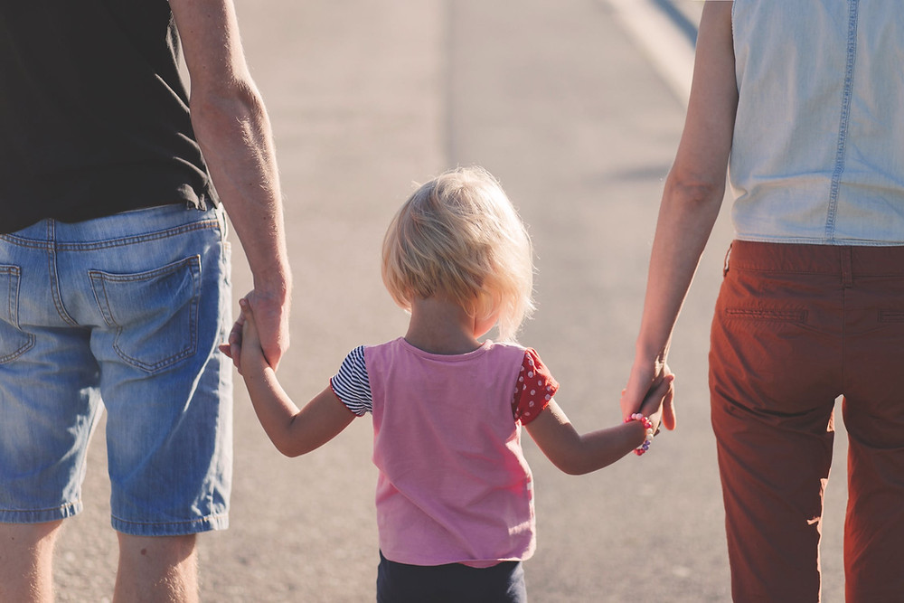 parents holding the hands of their child between them