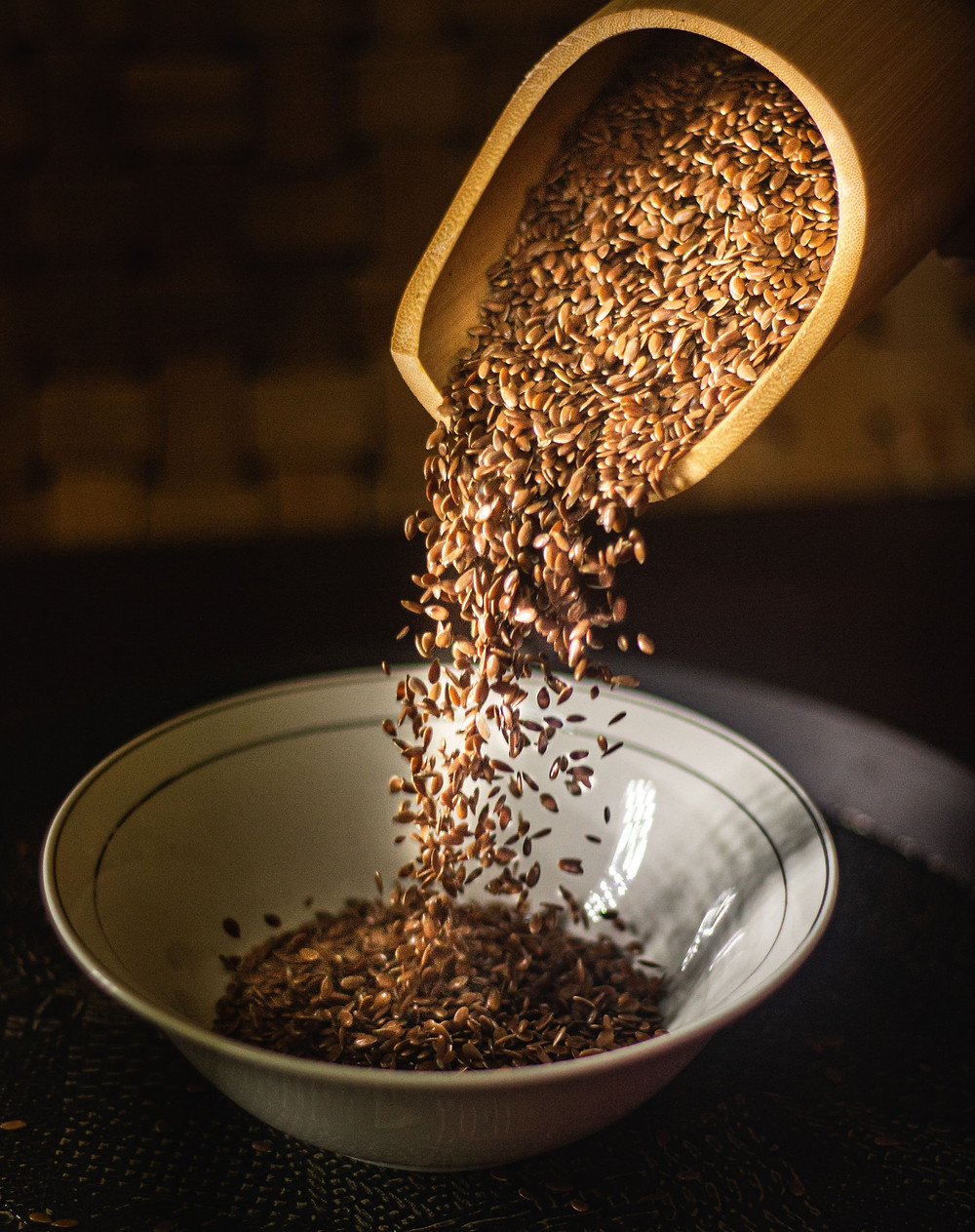 Somebody putting flax seeds into a bowl.