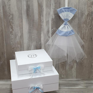Square cardboard boxes with initial and bow with tulle candle.