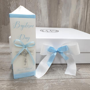 Square cardboard box with ring initial and silver resin cross.