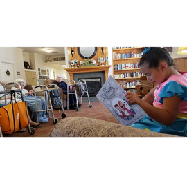 """Maya reads """"The Blossom Shoppe"""" at an elderly home."""