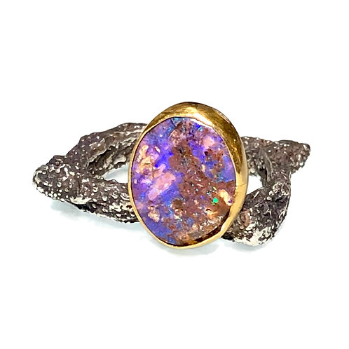 Boulder opal ring set in 18k gold on textured silver band