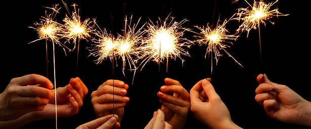 Six hands hold bright sparklers in the dark.