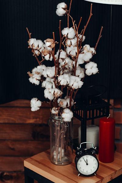 white-cotton-flowers-in-vase-beside-cloc