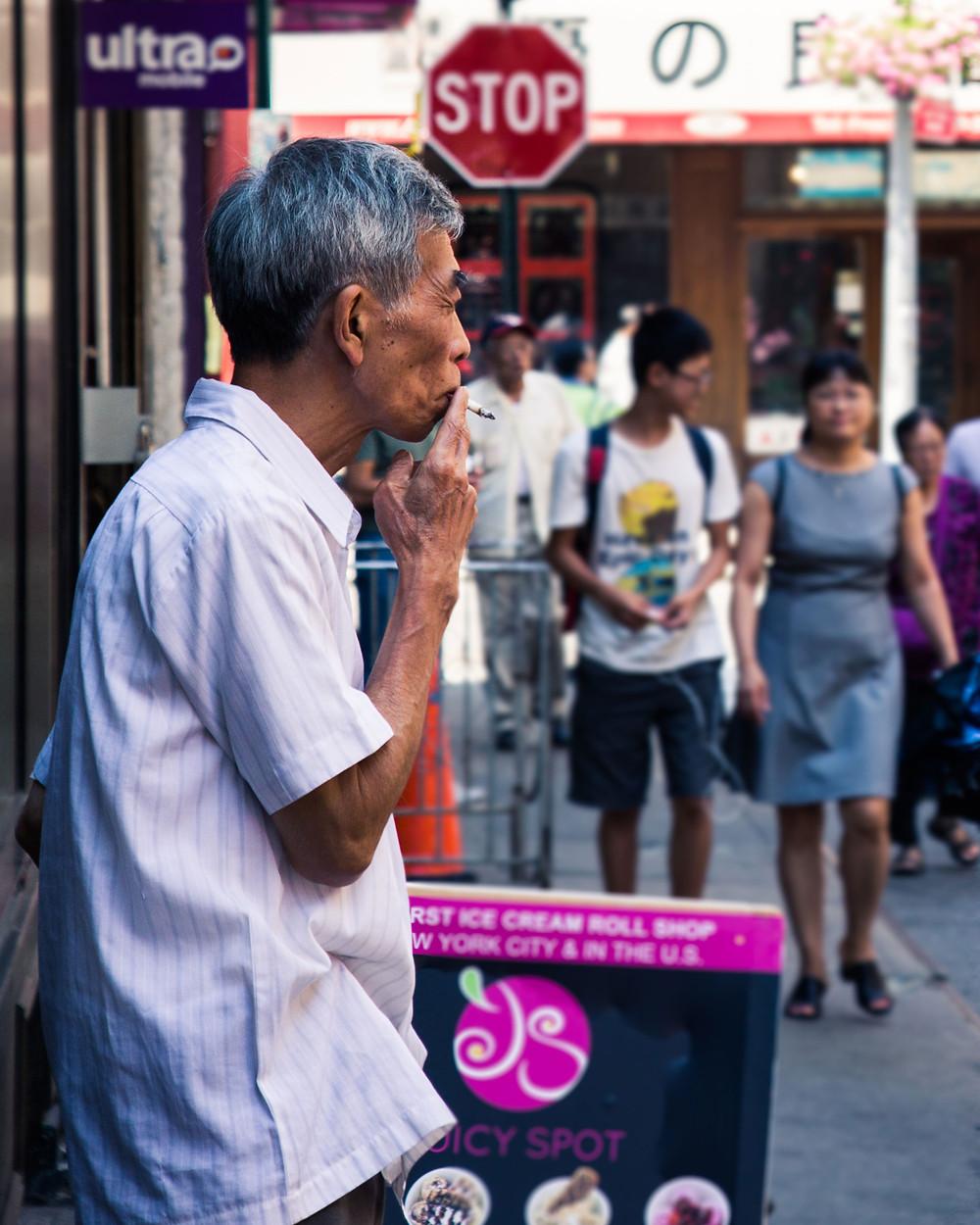 Elderly Chinese Man having a smoke break in Chinatown, Manhattan