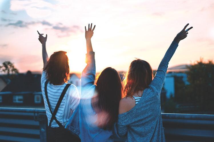 Teenagers waving to the sun setting on the horizon