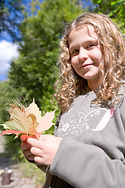 Caucasian girl, age 11-13, holds fall leaves in her hand agains the background of green trees and blue skies