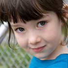 A Caucasian girl with brown hair and a blue shirt, 5-7 years old, standing next to a metal fence and looking into the camera