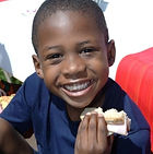 An African American boy age 8-10 in a blue t-shirt eating a sandwich