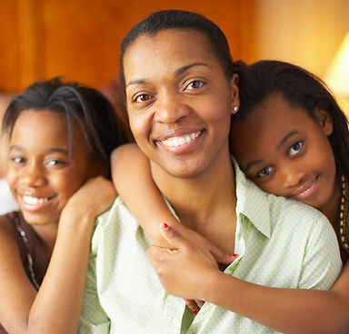 An African American woman wearing a green shirt looks at the camera as her two daughters, aged 10-12, wrap their arms around her from behind and gaze into the camera.