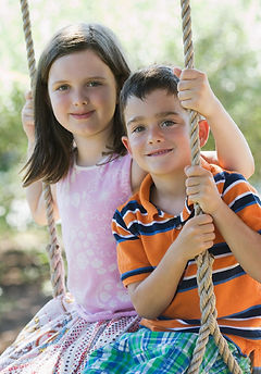 Two Caucasian children, a boy age 7-9 and a girl age 9-11, share a rope swing and smile into the camera