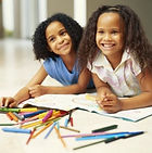 Two African American girls lay on their stomachs on the floor surrounded by colored pencils and coloring pads.  They smile at the camera.