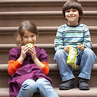 Two Caucasian children, a boy and a girl, enjoy a snack while sitting on bleachers