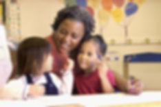 Middle-aged, heavyset African American woman with short locs holding two preschool girls in her lap