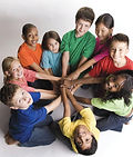 A diverse group of chidlren ages 10-12 placing their hands together in the middle of a group circle