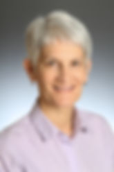 White woman with short gray hair in white sleeveless blouse