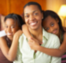 Middle-aged African American woman with two preteen daughters smiling and looking into camera