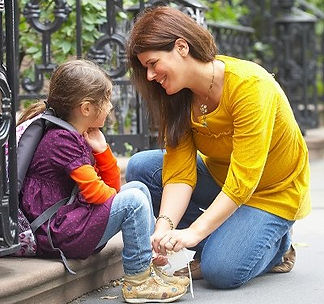 A Caucasian girl around age 7 wearing a backpack sits on a stoop.  A Caucasian woman around 35 squats down and smiles at the girl as she ties the girl's shoes.