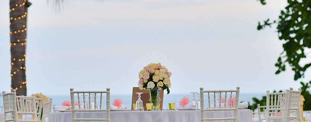 Wedding tableware at the beach featuring charger plates, tablecloth, and white chiavari chairs - Over The Moon Wedding & Event Rentals