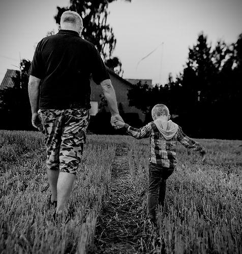 Man walking through field with boy