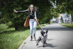 Young woman walking her dog on a street,