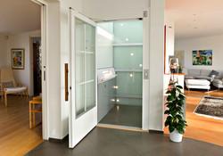 Glass home lift with open door