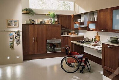Wheelchair in wooden disabled kitchen with lowered counters