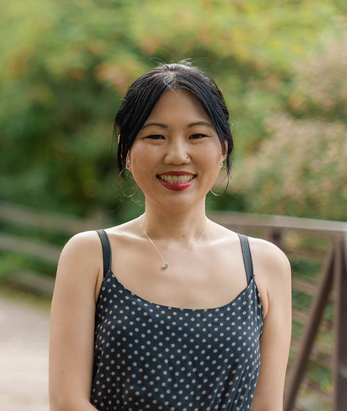 A photo of a smiling East Asian woman in a black slip dress with cream polka dots.