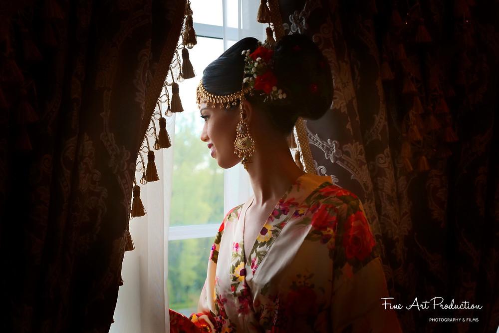 bride looking out of window at groom's baarat