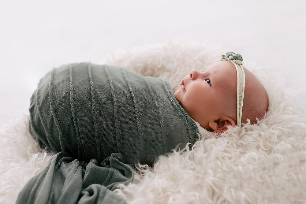 Newborn baby in green wrap and headband laying on fluffy rug