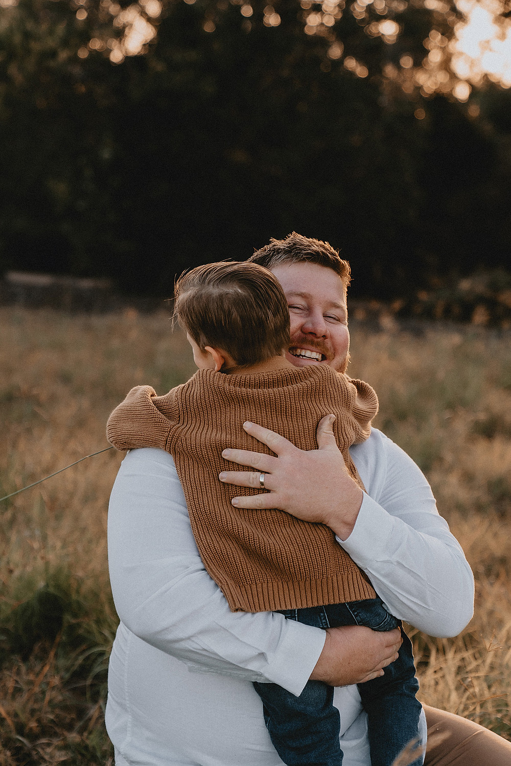 Father and son embrace in a hug in a sunny field with long grass