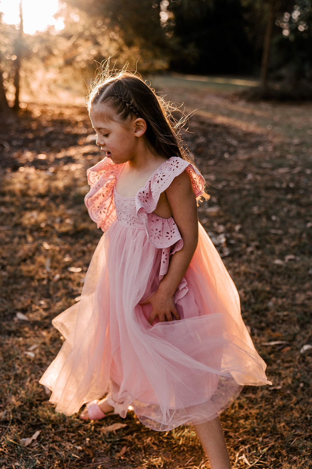 Girl in Pink Dress twirling in sunset